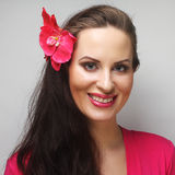 Happy woman with pink flower in the hair. Young happy woman with pink flower in the hair Royalty Free Stock Photography