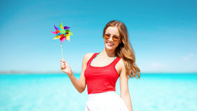 Happy woman with pinwheel over blue sky and sea. Summer holidays, travel, people and vacation concept - happy young woman in sunglasses with pinwheel over blue Stock Photo