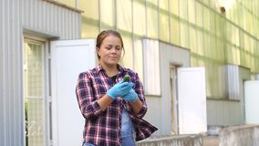 A female gardener in blue gloves is holding fresh cucumbers in a greenhouse. A happy woman in a plaid shirt holds a fresh cucumber in her hands against the stock footage