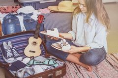 Happy woman planning a travel preparing a suitcase royalty free stock image