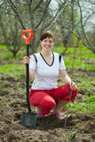 Happy woman planting fruit tree. In orchard Royalty Free Stock Photos