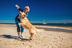 Happy woman playing on the beach with golden retriever Royalty Free Stock Photos