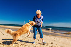 Happy woman playing on the beach with golden retriever Stock Photography