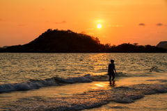 Happy woman playing on the beach at the sunset time Stock Photography