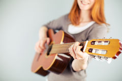 Happy woman playing a classical guitar Stock Image