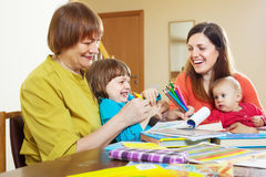 Happy woman playing with daughter and grandchildren. Happy mature women playing with daughter and grandchildren at table royalty free stock photography