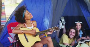 Woman playing guitar for her friends at a music festival 4k. Happy woman playing guitar for her friends at a music festival 4k stock video footage