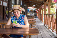 Happy woman is playing her mobile phone to communication with an Royalty Free Stock Image