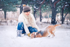 Happy woman playing with her pet in snow Royalty Free Stock Photos