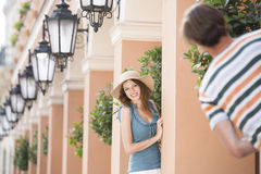 Happy woman playing hide-and-seek with man amongst pillars Stock Image