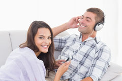 Happy woman playing music for man on mobile phone Royalty Free Stock Images