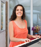 Happy woman playing piano at home Royalty Free Stock Photos