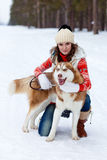 Happy woman playing with siberian husky dog in winter forest Royalty Free Stock Photography