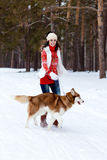 Happy woman playing with siberian husky dog in winter forest Stock Photo