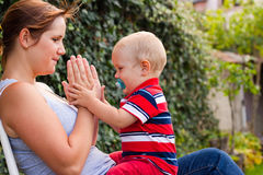 Happy woman playing with toddler boy outdoors Royalty Free Stock Image