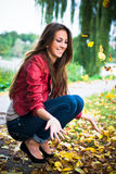 Happy woman playing with yellow leaves royalty free stock photo