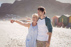 Happy woman pointing away with her son standing at beach Royalty Free Stock Photos