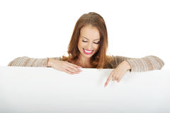 Happy woman pointing on blank board. Royalty Free Stock Photos