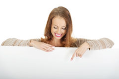 Happy woman pointing on blank board. Stock Image