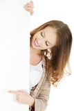 Happy woman pointing on blank board. Royalty Free Stock Images