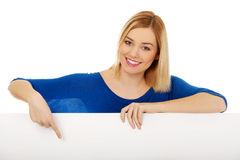 Happy woman pointing on blank board. Stock Photos