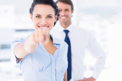 Happy woman pointing at camera with colleague in background Royalty Free Stock Images