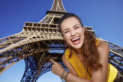 Happy woman pointing on Eiffel tower in Paris, France Stock Image