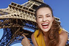 Happy woman pointing on Eiffel tower in Paris, France Stock Photos