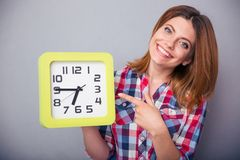 Happy woman pointing finger on clock Stock Photography