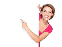 Happy woman pointing with her finger on banner