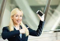 Happy woman pointing at her smart phone stock photos