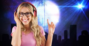Happy woman pointing while listening to music on headphones Stock Image