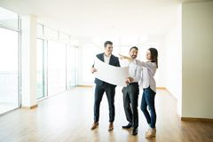 Happy Woman Pointing By Man And Agent In New Home. Happy women pointing away while standing by men and agent discussing over blueprint in new home stock photos