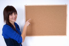 Happy woman pointing at the pin board. Stock Photography