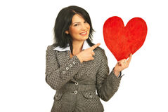 Happy woman pointing to heart shape Stock Photos