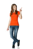 Happy woman pointing to the side standing in full length. Full length of young woman pointing to the side and looking there, isolated on white stock photo