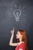 Happy woman pointing up and having an idea over blackboard Royalty Free Stock Photography