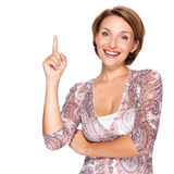 Happy woman pointing up with her finger Stock Photo