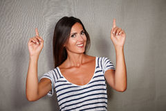 Happy woman pointing up while looking at camera Royalty Free Stock Image