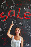 Happy woman pointing up at the sale advertisement drawn on black Stock Photography