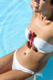 Happy woman in pool sunbathing Stock Images