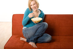 Happy woman with popcorn. A happy, laughing 29-year old woman sits casually on an orange sofa with her legs curled underneath, enjoying a bowl of hot popcorn Stock Photography