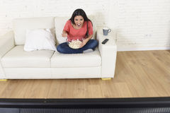 Happy woman with popcorn watching television at sofa couch happy excited enjoying comedy movie Stock Photography