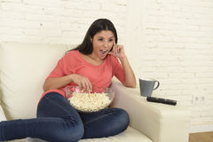 Happy woman with popcorn watching television at sofa couch happy excited enjoying comedy movie Royalty Free Stock Image