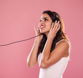 Happy woman. Portrait of a charming and beautiful woman listening to music in studio over pink background Stock Image