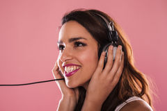 Happy woman. Portrait of a charming and beautiful woman listening to music in studio over pink background Royalty Free Stock Photos