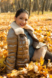 Happy woman posing in autumn leaves Stock Images