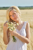 Happy woman posing with camomile in golden wheat. Royalty Free Stock Photo