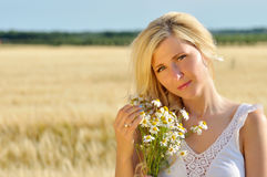 Happy woman posing with camomile in golden wheat. Royalty Free Stock Photography