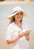 Happy woman posing with digital tablet at windy beach Royalty Free Stock Photography